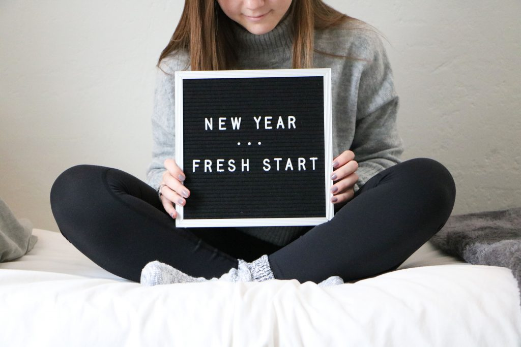 "blogger holding letter board that reads, ""new year ... fresh start"""