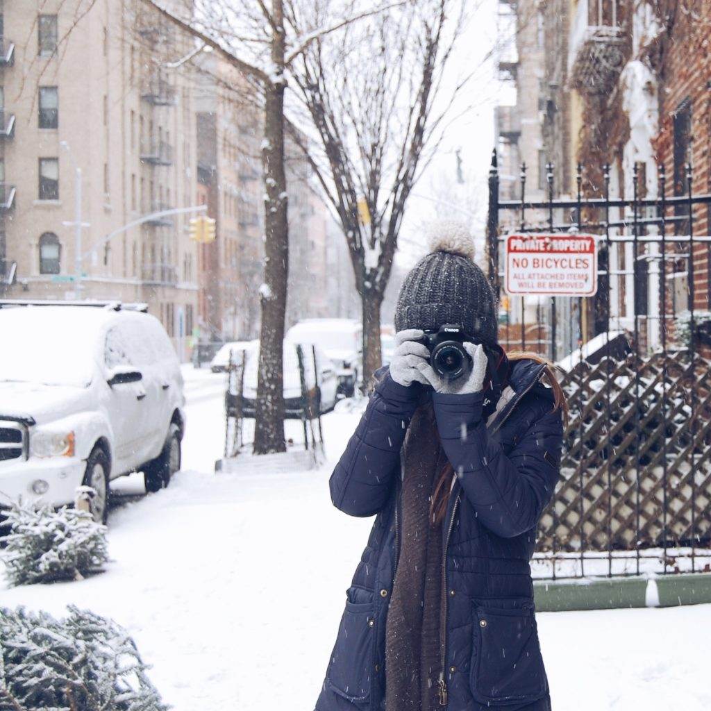 girl taking photo in snow